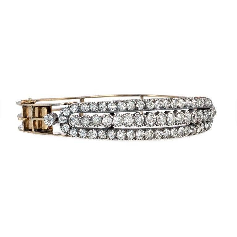 An antique half-hoop diamond bangle bracelet designed as an oblong, three-row openwork plaque, in 14K gold and sterling silver.  Atw 6.00 ct.  diamonds.  Dimensions: 6 1/2