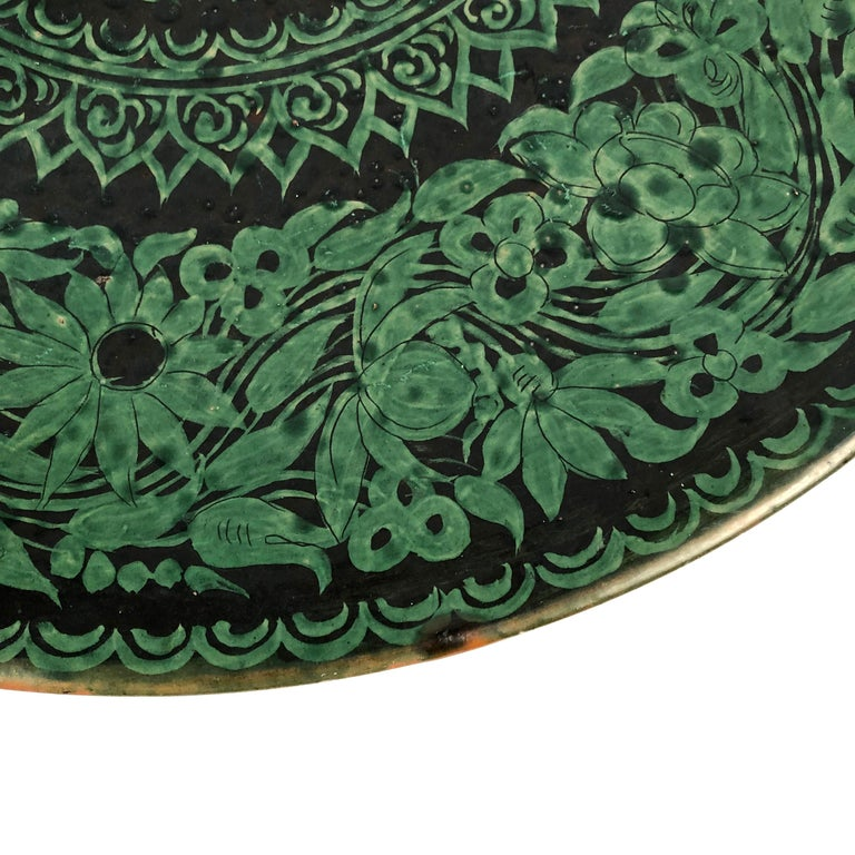 An antique 19th century Tibetan black and green slipware decorated charger, with wire on back for wall hanging, 18 1/2