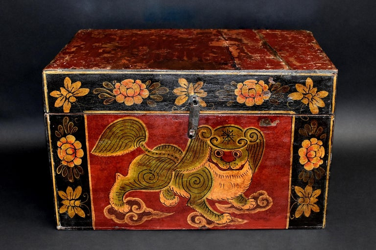 A wonderful, hand painted Tibetan box featuring a beautiful foo dog. The foo dog is of the Pekingese breed with perfect hair and posture. He looks to his right with great curiosity and intent. All four paws on clouds adds a celestial appeal. Border