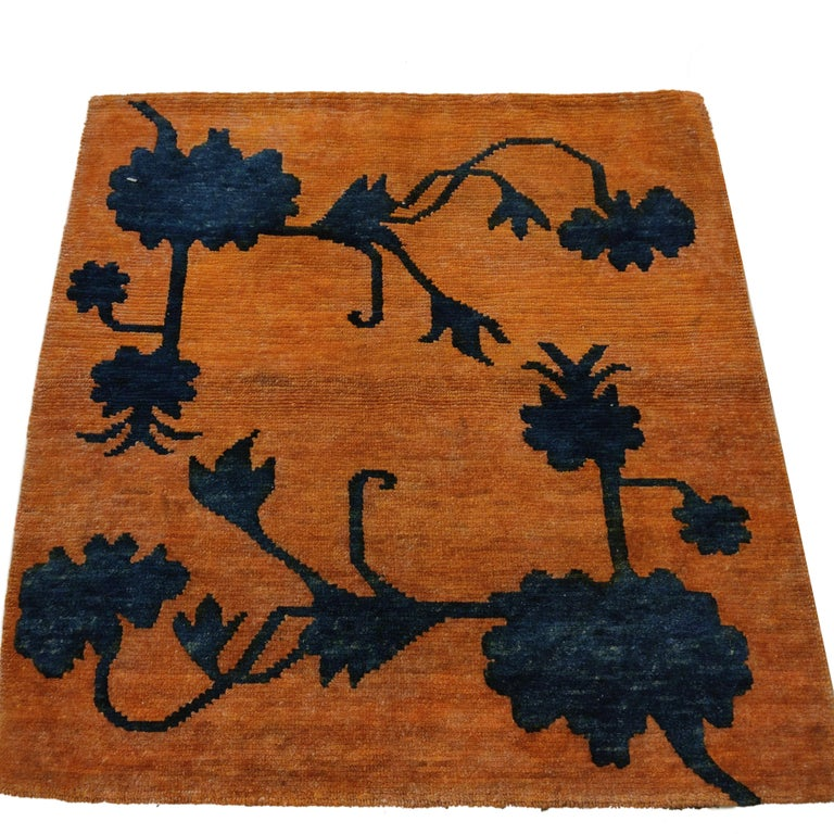 A very finely woven, jewel-like antique Tibetan rug distinguished by a pattern of indigo blue lotus flowers, symbols of purity, rendered in relief on an orange background. Rugs of this type are called buma rimo (from the Tibetan 'cut like a