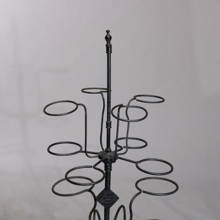 An antique garden plant display stand offers wrought iron construction with tiered scrolled arms terminating in pot receivers, raised on four legs, circa 1890  Measures: 53.25