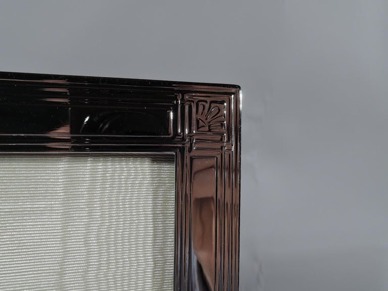Art Deco sterling silver picture frame. Made by Tiffany & Co. in New York, circa 1920. Rectangular window in flat surround with acid-etched rectilinear frames on sides and front; corners interlaced with stylized leaf. With glass, silk lining, and