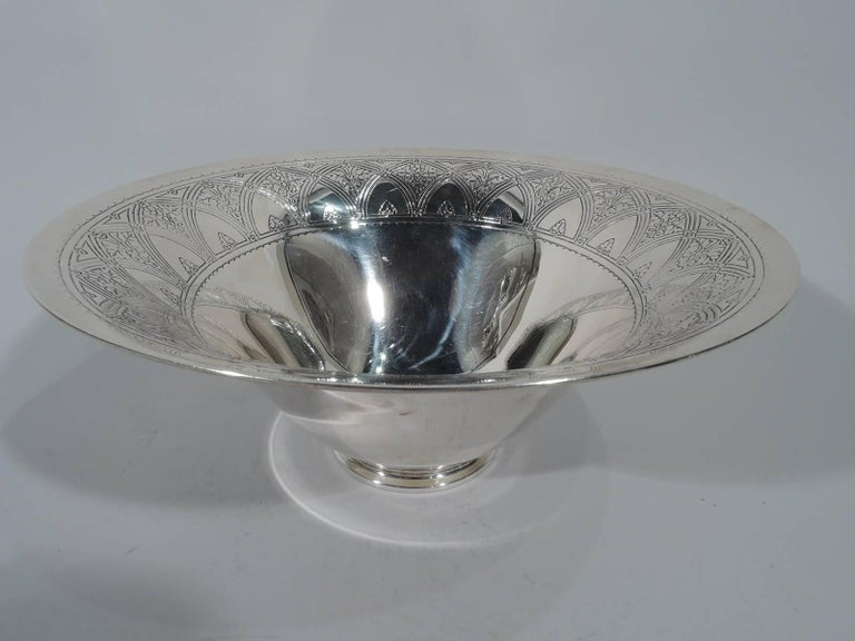 Art Deco sterling silver centrepiece bowl. Made by Tiffany & Co. in New York, circa 1924. Wide mouth, steeply tapering sides, and stepped foot. Interior has acid-etched interlaced arcade inset with flowers and scalloped border. A semi-abstract