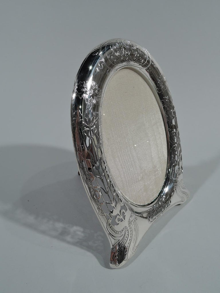 Art Nouveau sterling silver picture frame. Made by Tiffany & Co. in New York. Oval window in curved horseshoe-form surround with bracket feet. Semi-abstract fluid, sinuous flowers and interlaced tendrils. At top stylistically-integrated interlaced