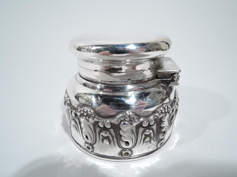 Art Nouveau sterling silver traveling inkwell. Made by Tiffany & Co. in New York. Round bowl with applied scrolling leaf and berry border, and curved shoulder. Cover flat, hinged, and overhanging. Bowl interior glass lined with poignant evidence of