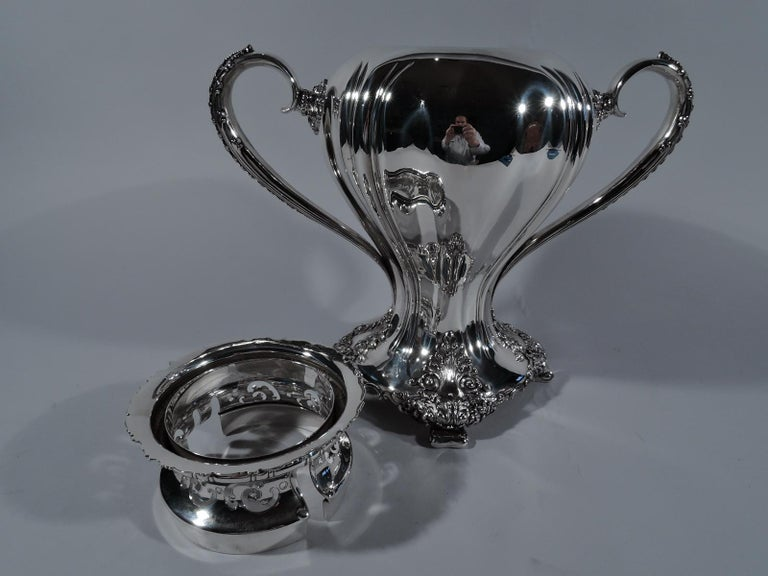 Heavy Classical sterling silver trophy cup. Made by Tiffany & Co. in New York. Swooping baluster flowing into four curved-sided base on splayed volute supports. Leaf-capped and mounted reeded scroll side handles. Slash gadrooning. Acanthus leaves