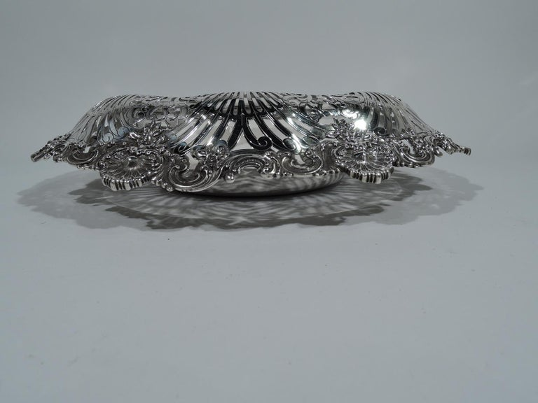 Edwardian sterling silver small centerpiece bowl. Made by Tiffany & Co. in New York, circa 1910. Solid round well with wide and wide turned-down sides with pierced dynamic scrolls and shells, flowers, and scrolls applied to rim. Sumptuous. Hallmark