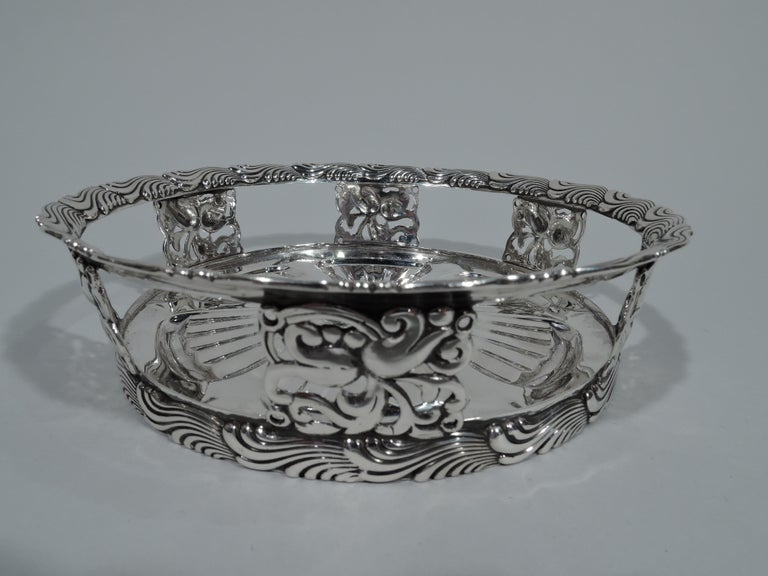 Stylish sterling silver wine bottle coaster. Made by Tiffany & Co. in New York. Solid well with fluted and radiating leaf and dart ornament. Open sides with blocks comprising pierced scrollwork and flowers. Flared rim with chased and fluid wavy