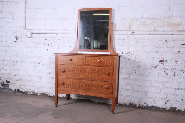 A gorgeous antique tiger oak dresser with swing mirror, circa 1900. The dresser features stunning tiger oakwood grain and quality American craftsmanship. It offers good storage, with four deep dovetailed drawers. Included is the swinging vanity