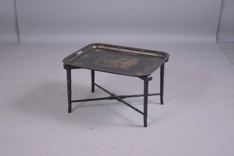 An extraordinary 1900s tole tray table, the top is crafted of metal, features trim details around the tray a fruit basket in the center. The top sits on a vintage wood base with faux bamboo design with its original ebonized finish, only cleaned and