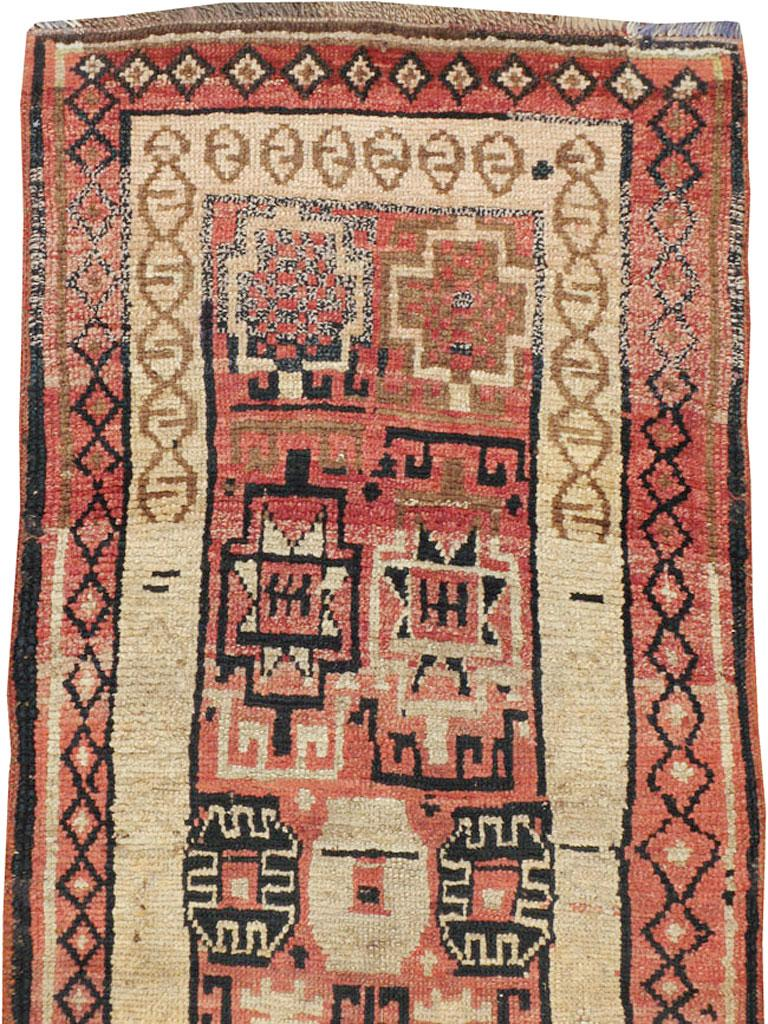 An antique Turkish Anatolian runner from the early 20th century. Anatolian, the rose-red field displays a geometric pattern of Memling guls (flowers), stars, cartouches-in-boxes and other hard to describe motives because of the rugs Primitive