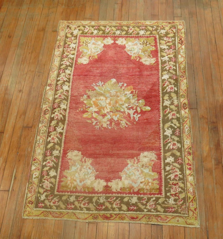 Gorgeous soft colored antique Turkish ghiordes rug with a floral open medallion design and floral border.