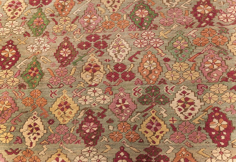 Antique Turkish Ghiordes rug (size adjusted) in beige, green, orange, pink, red, and yellow. Size: 10'5