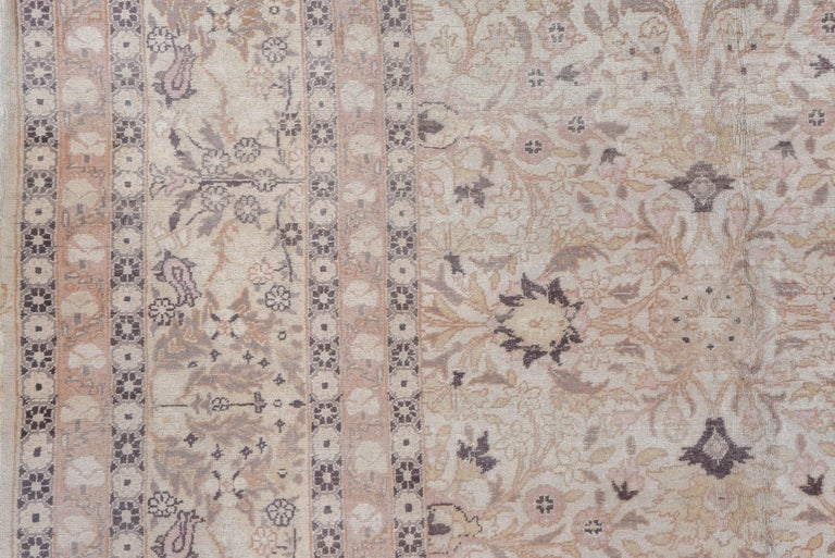 The ivory field of this urban western Turkish antique carpet shows a centralized, four part pattern of sharp petal palmettes, tulips, flower sprays and vinery detailed in corresponding lighter tones, with a sand border of complete flowers, tulips