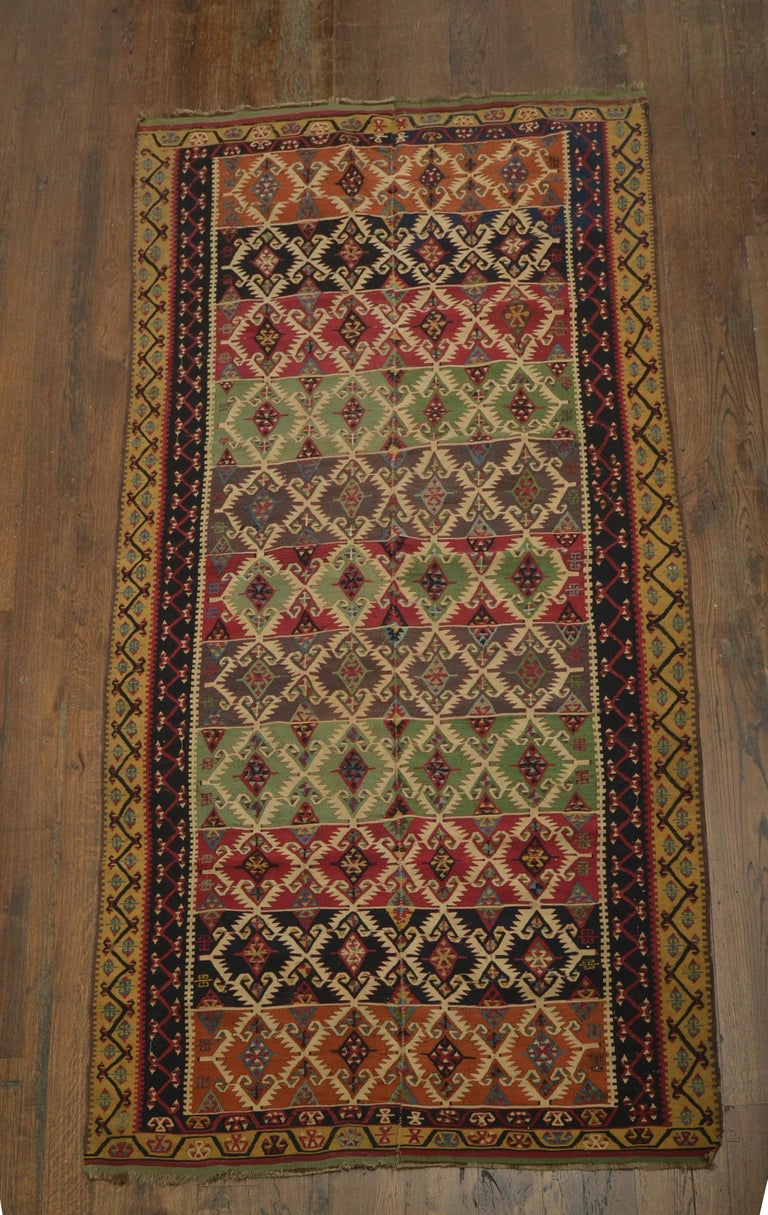A rare original fine Turkish Kilm woven in two panels. Extraordinary vegetable dye colors of green, gold, navy and cochineal dyes. Intricate multiple borders of vine designs.