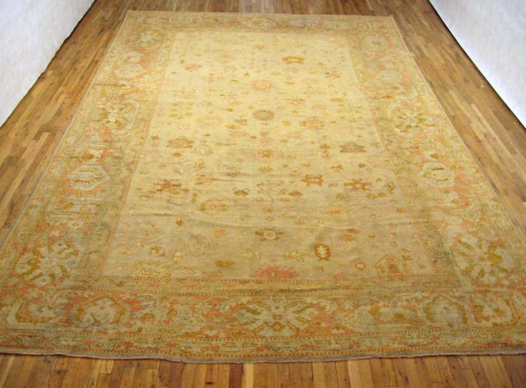 An antique Turkish Oushak carpet, circa 1900. Size: 17' x 11'. This lovely carpet has a variety of floral motifs across the softly hued central field. Enclosed within a festive border that gives this informal carpet even more of a sense of whimsy