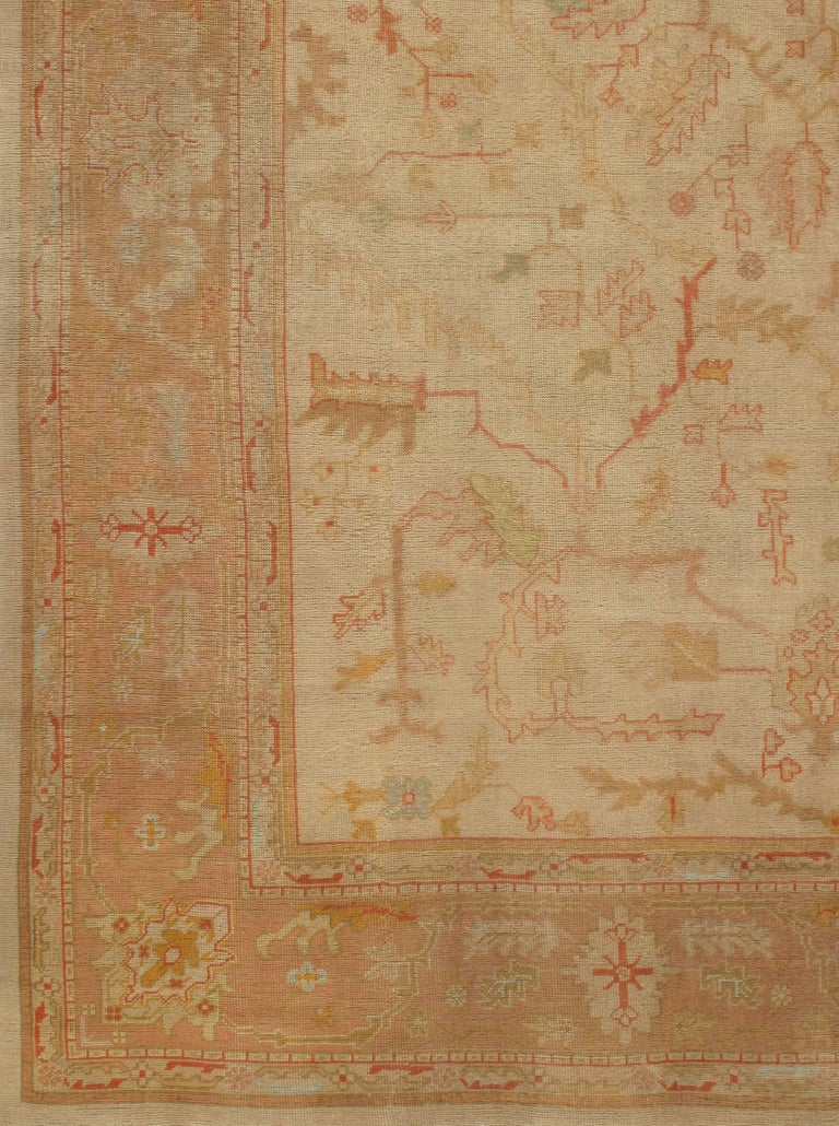 Antique Turkish Oushak rug, circa 1890. Organic botanical patterns woven in soft pastels play across the cream central field on this antique Oushak rug from Turkey. A soft auburn border containing floral patterns woven in soft pastels actualizes the