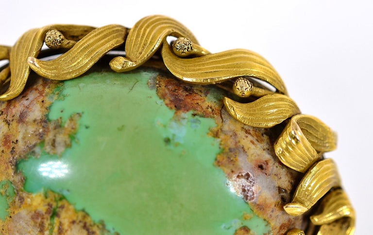 A unique Art Nouveau  natural green Turquoise oval brooch.   The Turquoise flaunts its organic golden inclusions and is set in a 14KT yellow gold frame of flowing leaves, enhanced by a time worn soft patina.  The brooch can also be worn as a