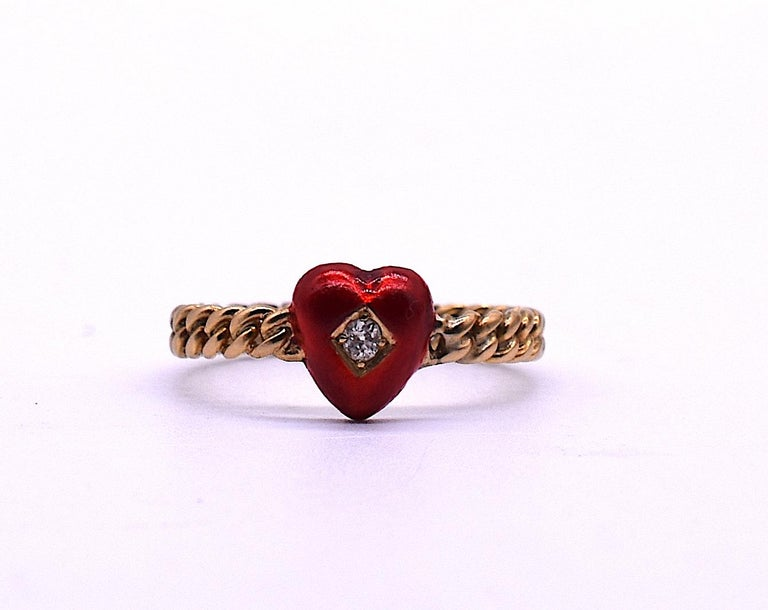 18K Edwardian gold band ring featuring a lovely enamel red heart with a round diamond embedded in a diamond shape at the center. The ring is enhanced by its the twisted rope band. We love the burst of color the little red heart adds as well as the