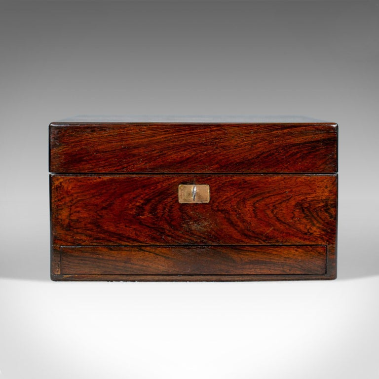 This is an antique vanity box. An English, Victorian travelling vanity case in rosewood and dating to the mid 19th century, circa 1850.