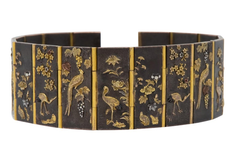 Scrolling imagery of flowers and water fowl on each patinaed link, joined together by gold hinges  Completed by concealed clasp  Tested as 14 karat gold   With maker's mark  Circa 1880's  Length: 7 inches  Width: 15/16 inch  Total Weight: 64.3