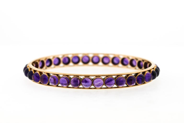 Unusual and easy to wear, this antique Victorian gold bangle set with cabochon amethysts is attractive and versatile. The concentric amethysts set all the way around the oval bangle is unusual with such a modern aesthetic. The bracelet is very easy