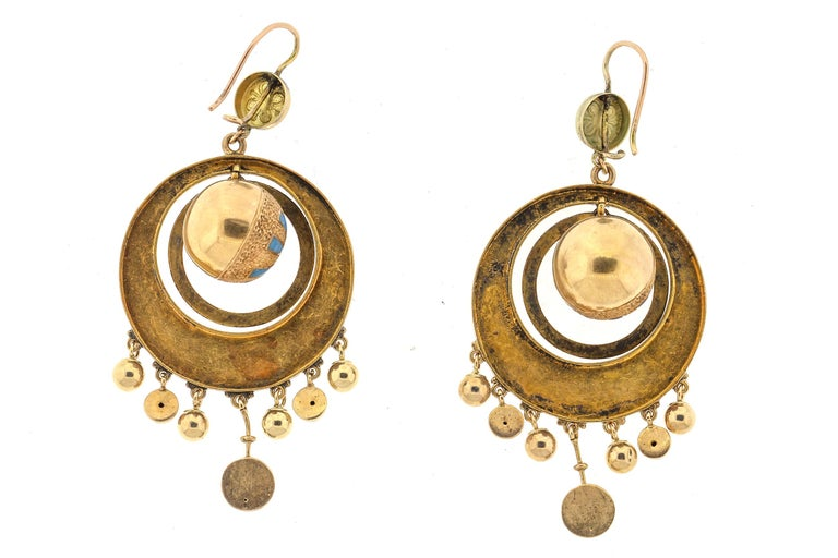 A swingy pair of Victorian 14k gold blue enamel drop earrings. These earrings are several moving circles surrounding a ball with fringe dangles on the outer circle. Quite a design of fun moving earrings. The blue enamel accents only add to these