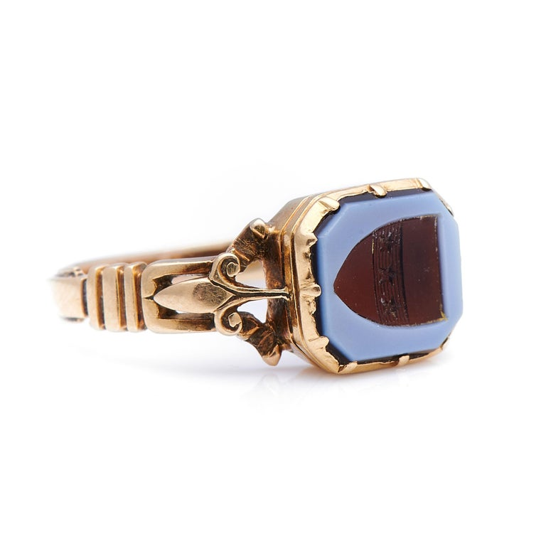 Carved agate signet ring, circa 1880. A striking ring, a beautiful carved agate, depicting a family crest, sits to centre in a simple but visually stimulating ribbed rub-over setting with skilful Fleur-de-lis style gold work shoulders; a true