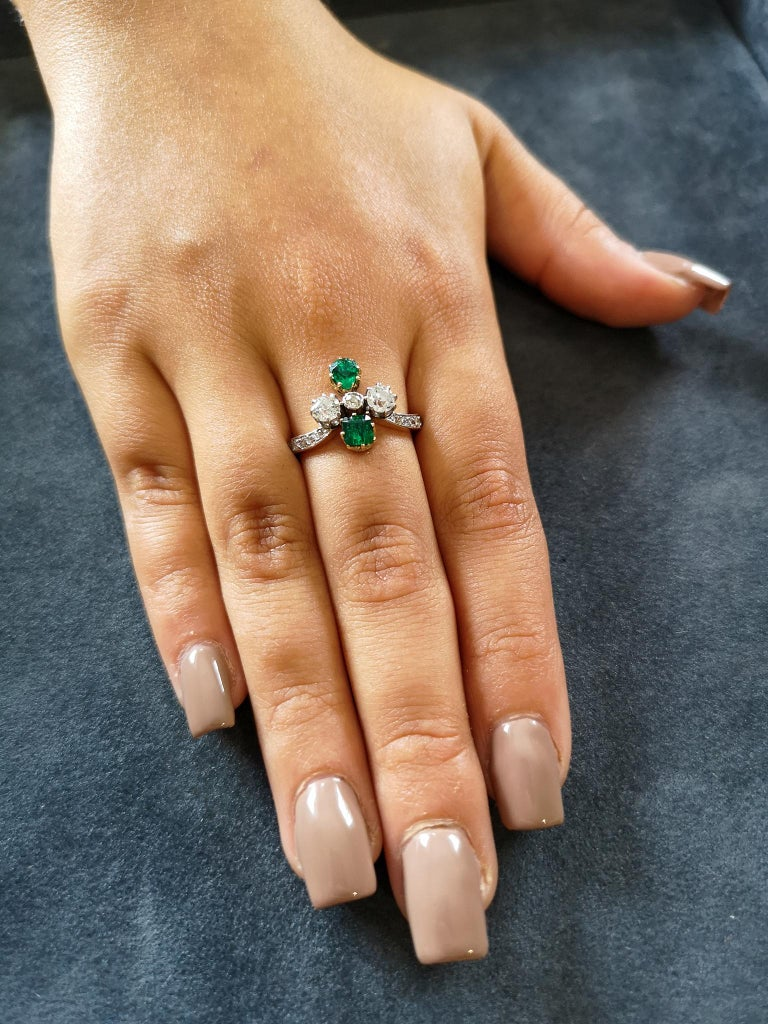 An exquisite Victorian ring circa 1890, featuring a pavé diamond-set, wishbone shaped shank, adorned with a cluster of square and pear-shaped emeralds and round diamonds, all mounted in 18 carat gold claws. Approximately 0.75 of a carat of
