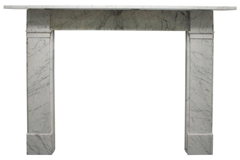 An antique late 19th century Victorian fireplace surround in carrara marble of simple unadorned form. Square capitals above plain jambs and foot blocks.