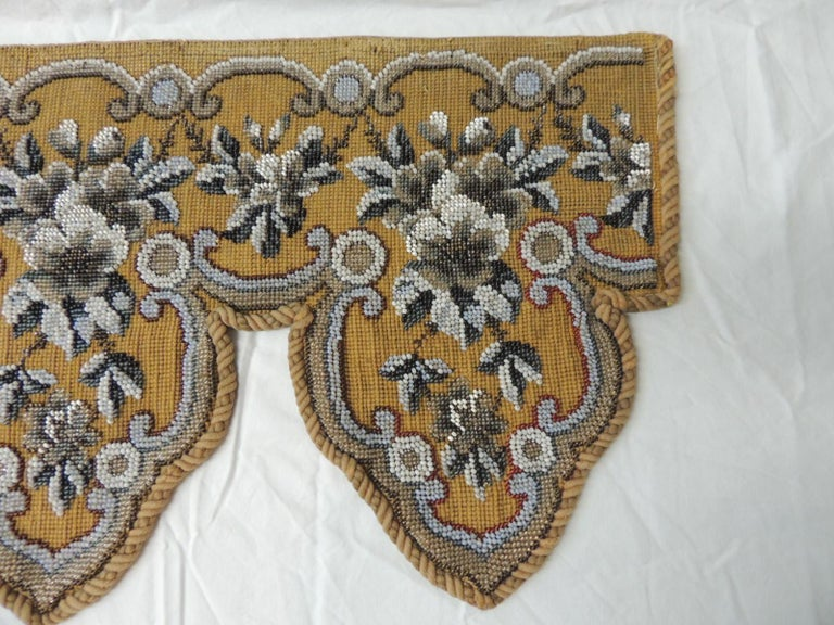 Gray white brown and gold glass beads embroidered on a tapestry and framed with antique rope trim.