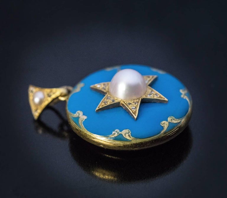 Circa 1870  An antique Victorian 14K gold star-motif locket pendant is embellished with glossy turquoise blue enamel, two half pearls, and tiny old mine cut diamonds. The back is set with a glazed compartment.  Diameter 25 mm (1 in.)  Sold without
