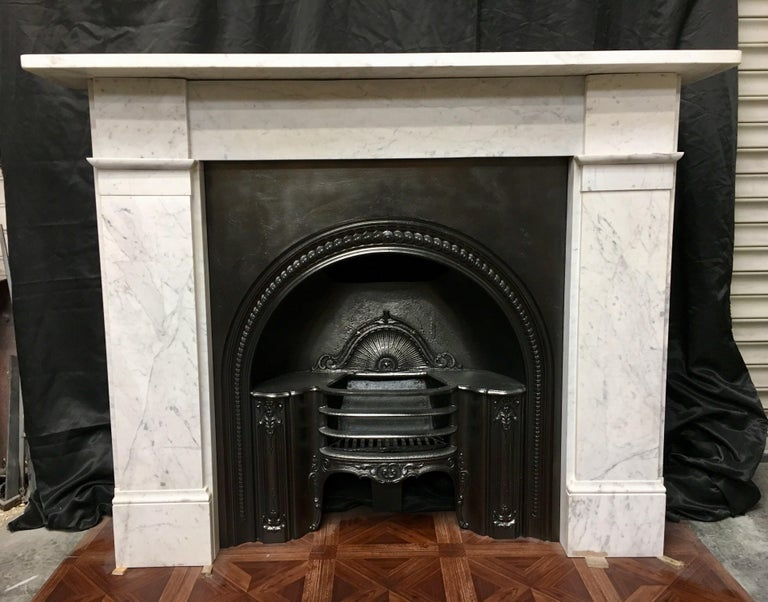 A simple, but attractive Classic antique Victorian Carrara marble fireplace surround, a square shelf sits above a plain frieze, flanked by a pair of unadorned jambs with block and moulding to the lower frieze level, finishing on moulded foot