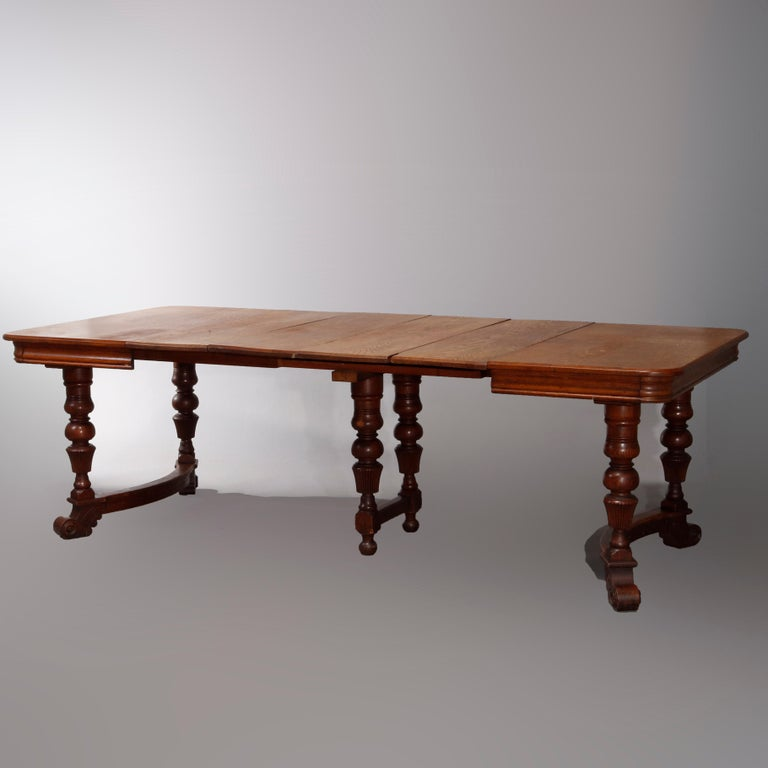 An antique Victorian extension dining table offers oak construction with carved balustrade legs having conve stretchers and scroll feet, includes four leaves, circa 1900  Measures: 28.5