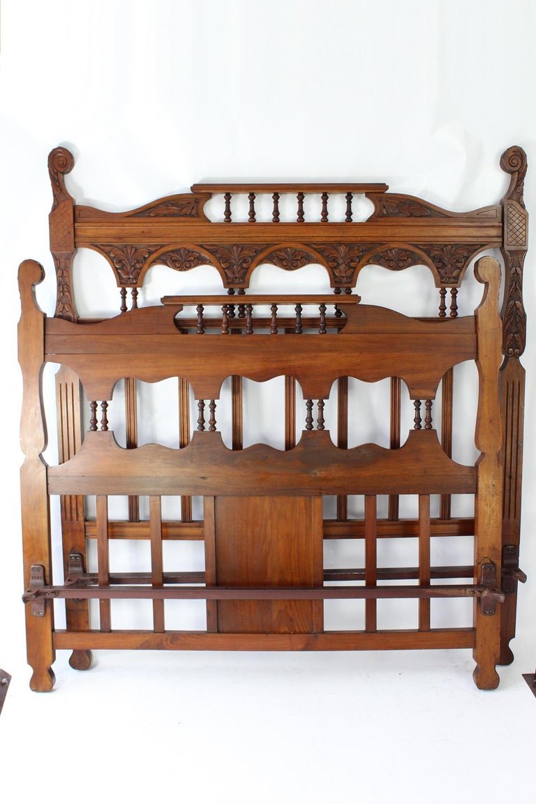 A truly magnificent antique Victorian carved walnut double bed dating from circa 1895. In a richly figured walnut, with attractive foliate carving throughout. Featuring carved top rails with turned twin pilaster supports and vertical slats, the