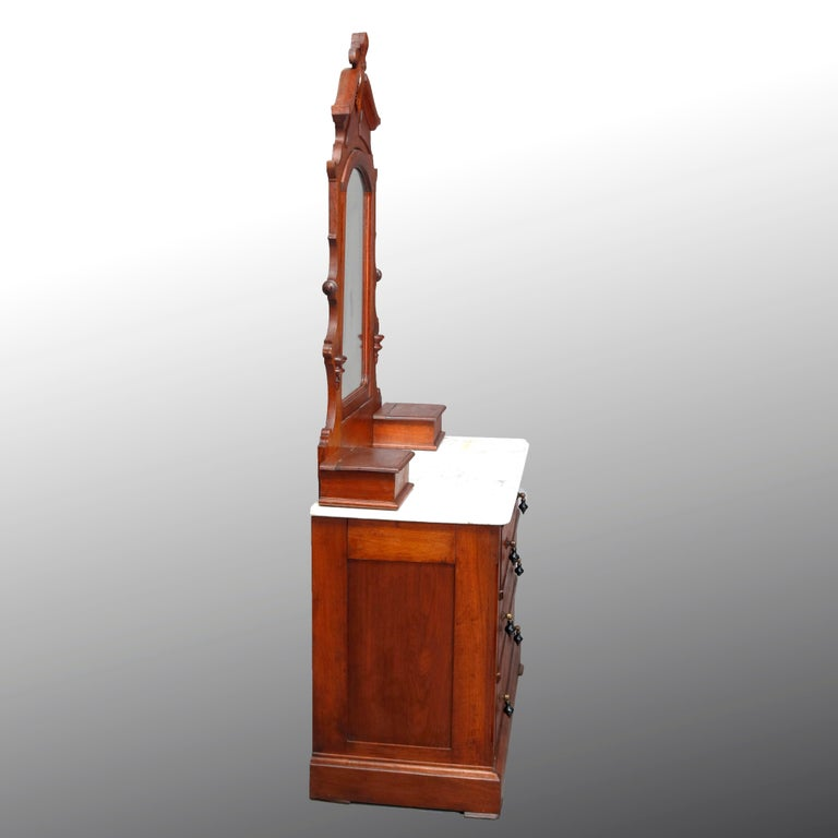 An antique Victorian dresser offers walnut construction with a tall mirror having frame with carved fleur des lis crest surmounting base with flanking lift-top glove boxes on a case with marble top and three long drawers each having tear drop pulls,
