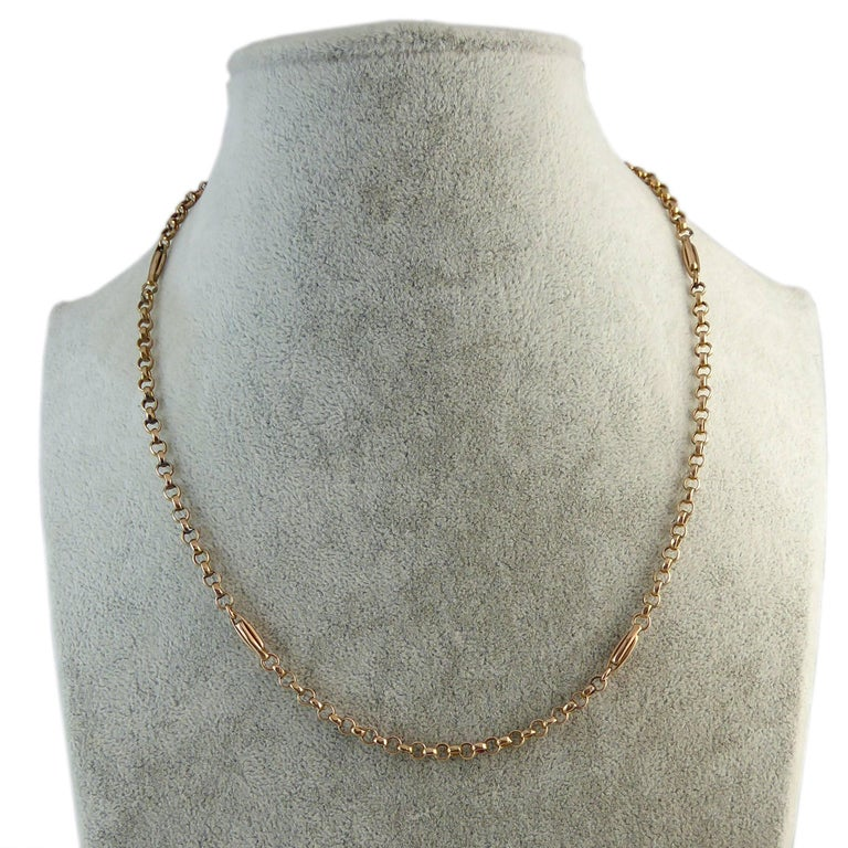 An antique gold chain comprising round belcher links that is lifted from the ordinary by the occasional placement of two entwined elongated oval gold links.  The chain is a very useful 17 inches in length so it shows nicely when worn with an open