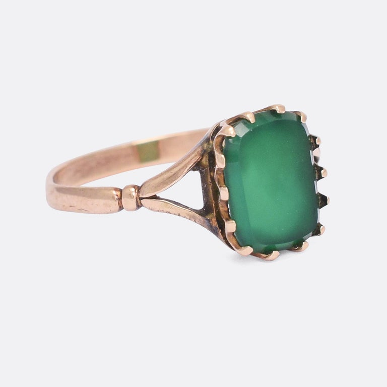 A pretty antique signet ring set with a cushion shaped green chalcedony panel in a simple claw mount. It dates from the turn of the 20th Century, circa 1900, modelled with split shoulders, and in 9 karat gold throughout.  STONES  Chalcedony Panel