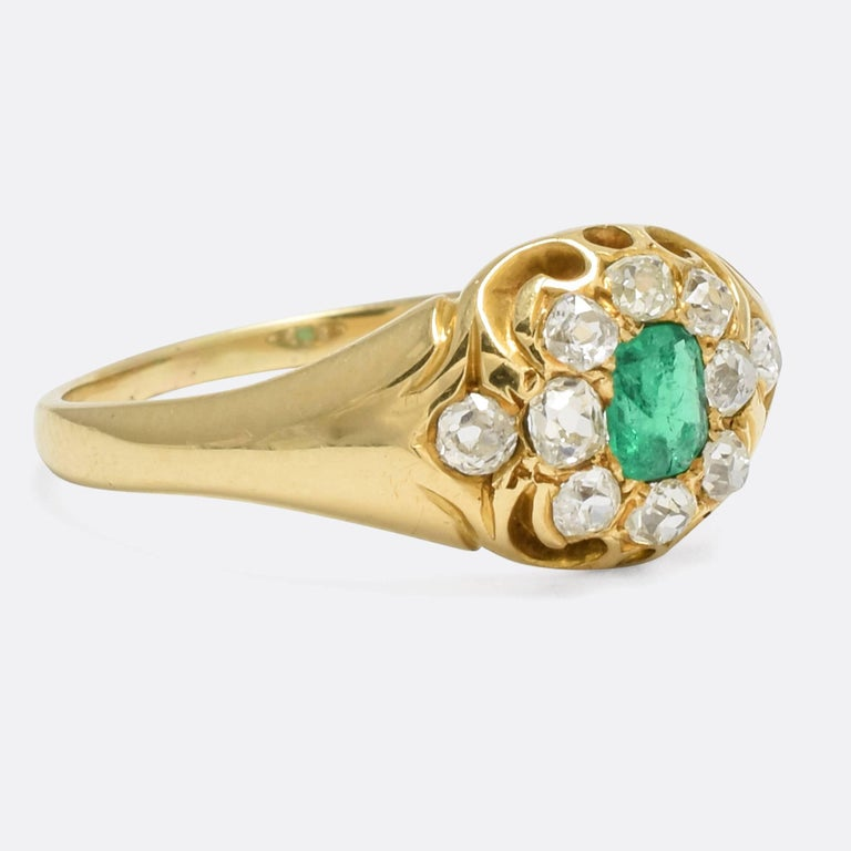 A beautiful antique cluster ring set with a vibrant emerald and ten old mine cut diamonds. The pierced gallery displays chased scroll detailing, and the ring is modelled in 15k gold throughout. A fine piece, the design is very typical of the late