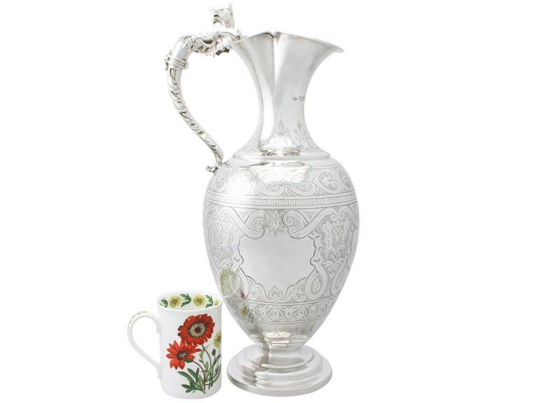 A magnificent, fine and impressive, large antique Victorian English sterling silver wine ewer; part of our wine and drinks related silverware collection.  This magnificent antique Victorian English sterling silver wine ewer has an ovoid shaped