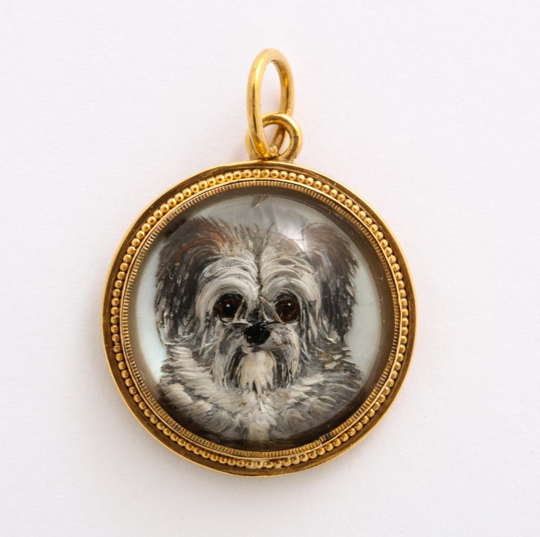 Just look at the face on this pendant of a precious Essex crystal terrier pup set in gold and you will want to hug it. The dogs big round eyes beg your attention. The dog seems to jump from its containment. Essex crystal or reverse crystal intaglio,