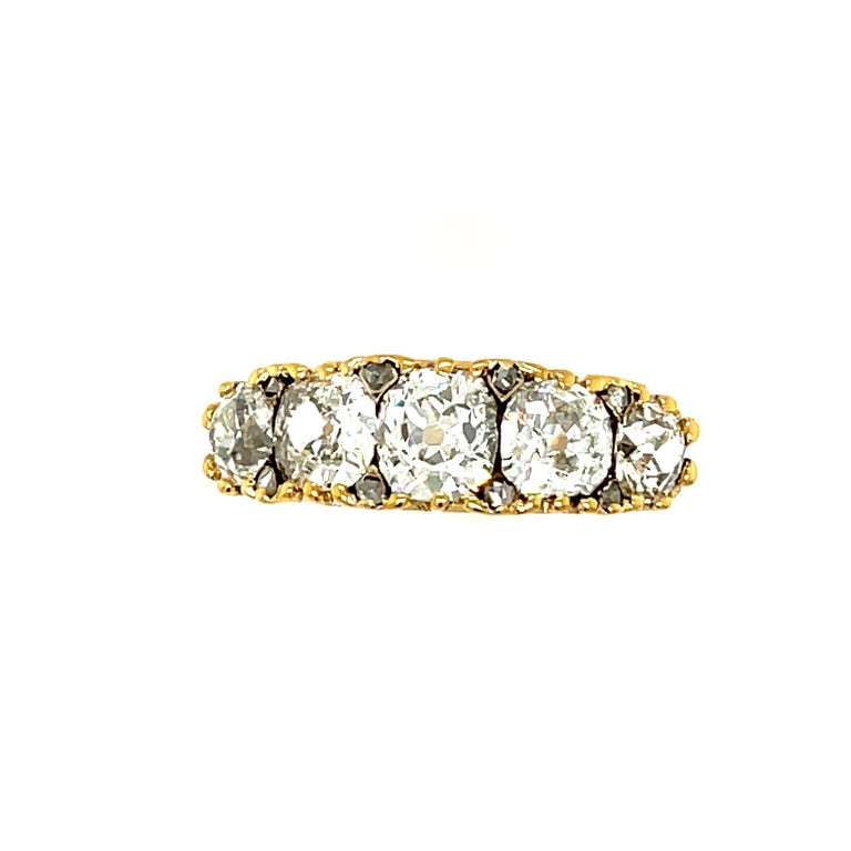 An antique Victorian 18k gold five stone old mine diamond half hoop ring, circa 1870. The ring is set with chunky old cut stones that are not round but cushiony in shape. This creates the look of the stones being particularly close together without
