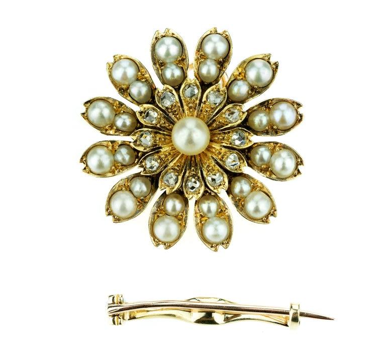 A fine Victorian eighteen carat gold, diamond and natural saltwater pearl pendant with a detachable brooch fitting. Designed as a flower head, the central pearl is bordered by rose cut diamonds, with a further double row of pearls creating the
