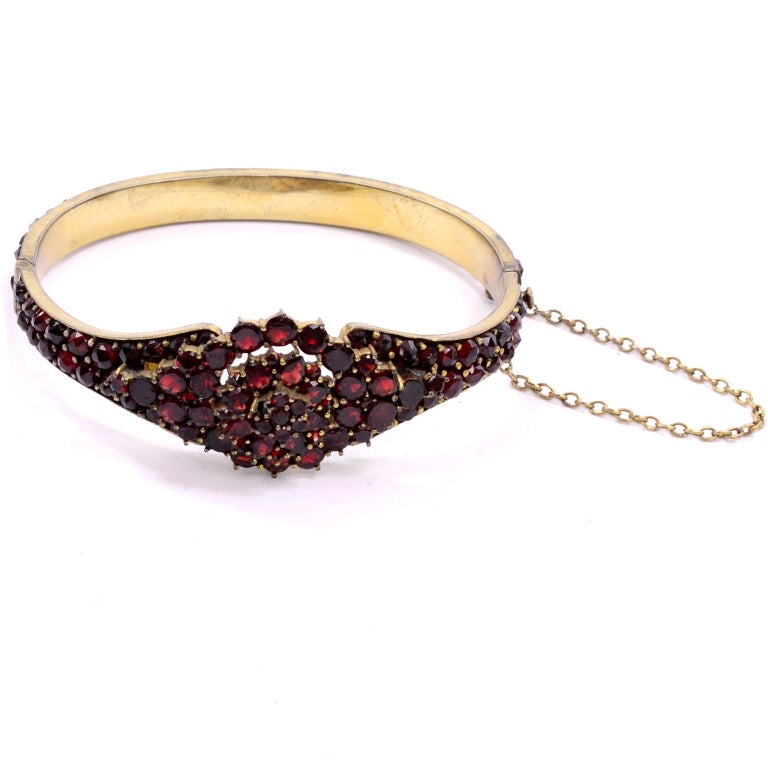 Rich red garnets cover this beautiful hinged clamper bracelet from the early 1900's. This bracelet has a chain connector and is gold tone metal. The center is a three tiered cluster of round stones, creating a floral motif.  INSIDE WRIST: 6.5
