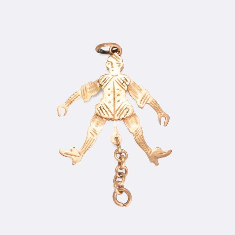A cute antique novelty pendant modelled as a jester. The piece is articulated: when the chain at the bottom is pulled, the arms shoot up and the legs kick out. It's crafted in 9k gold and features hand-chased detaling to the face and