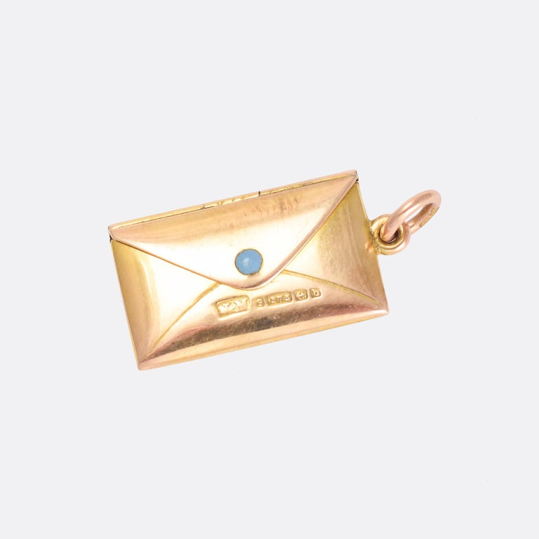 Such a sweet antique locket modelled as an envelope with the name Bobby engraved onto the front. It opens up to reveal a letter with the words I LOVE YOU on one side, and signed John on the back. It's crafted in 9 karat gold and set with a single