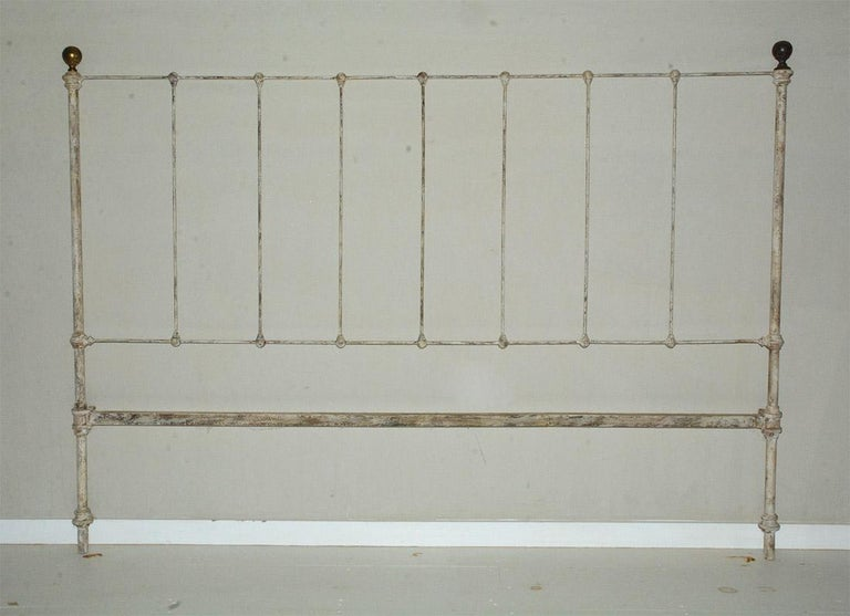 Antique country style white painted cast iron king size headboard with brass finials. Wonderful Classic simple style that will lend itself to modern, classical, neoclassical, Swedish Gustavian or French country decor. Search term: King bed.