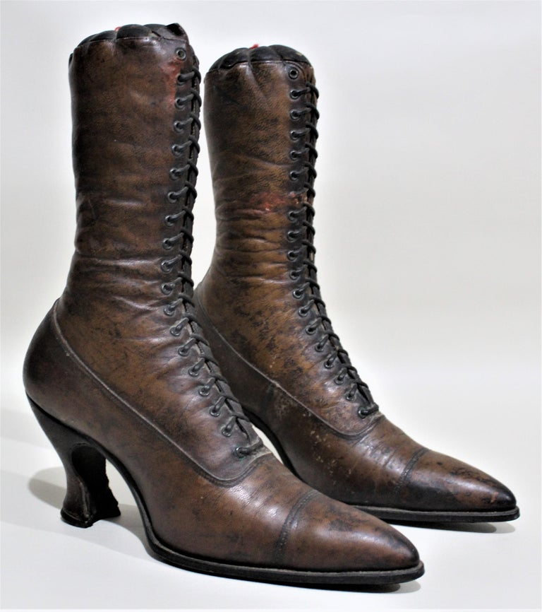 Pair of antique Victorian ladies high boots constructed of brown leather and used as mercantile models for a store display. Each sole has an impressed mark of
