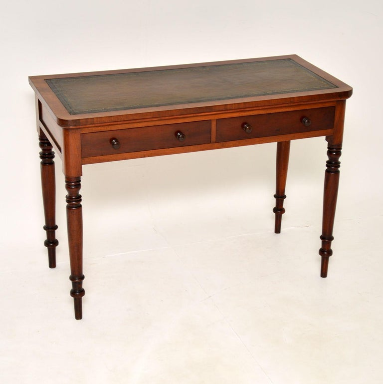 An excellent antique early Victorian writing table, made in England & dating from around the 1840-1860's period.  It is a great size and is extremely well made. The inset leather top has been hand coloured and gold tooled. There are panelled