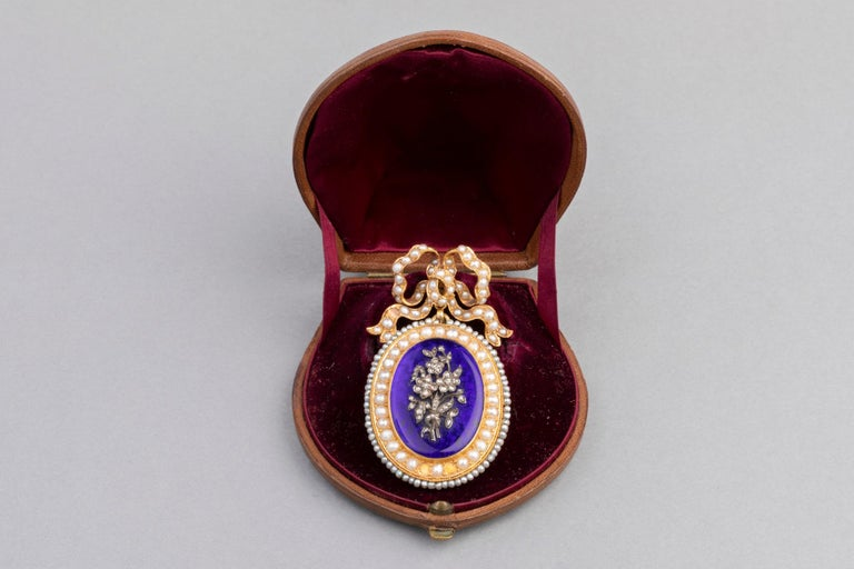 Very Beautiful antique Locket. Made in France circa 1850.   Mounted in Yellow Gold 750 (French hallmark: eagle, mark of the maker)  Covered with blue enamel and Natural pearls.  Floral theme with rose cut diamonds.  Some pearls are missing and are